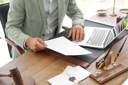 Photo pour Male notary with documents and laptop at table in office, closeup - image libre de droit