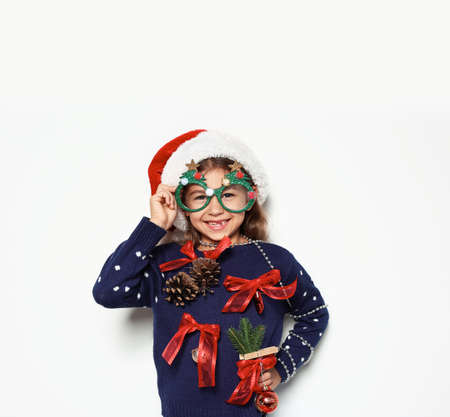 Photo for Cute little girl in handmade Christmas sweater and hat with party glasses on white background - Royalty Free Image