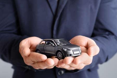 Photo pour Male insurance agent holding toy car on grey background, closeup - image libre de droit