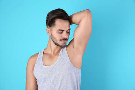 Photo for Handsome young man showing armpit on color background. Using deodorant - Royalty Free Image