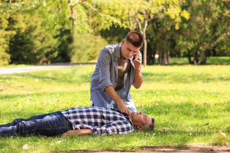 Foto de Passerby calling ambulance while checking pulse of unconscious man outdoors. First aid - Imagen libre de derechos