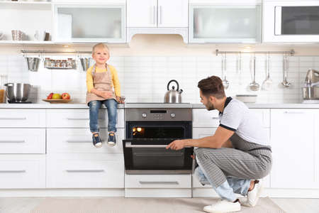 Photo pour Young man and his son baking something in oven at home - image libre de droit