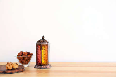 Photo for Muslim lantern Fanous and dried fruits on table against light background. Space for text - Royalty Free Image