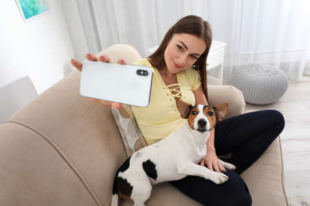 Photo pour Beautiful woman taking selfie with her dog on sofa at home - image libre de droit