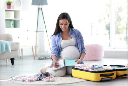 Photo pour Pregnant woman writing packing list for maternity hospital at home - image libre de droit