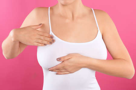 Woman checking her breast on color background, closeup