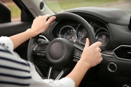 Foto de Woman holding steering wheel in car, closeup. Driving license test - Imagen libre de derechos