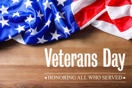 Text VETERANS DAY and USA flag on wooden background, top view. Honoring all who served