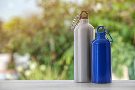 Photo for Sports water bottles on table against blurred background. Space for text - Royalty Free Image