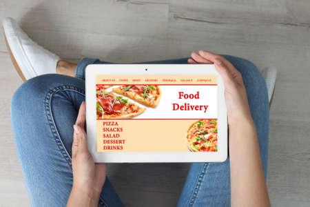 Foto de Woman using tablet to order food delivery at home, top view - Imagen libre de derechos