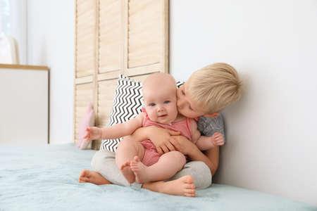 Photo pour Cute boy kissing his little sister on bed at home - image libre de droit