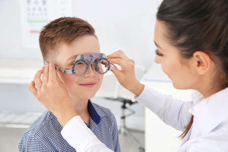 Foto de Children's doctor putting trial frame on little boy in clinic. Eye examination - Imagen libre de derechos