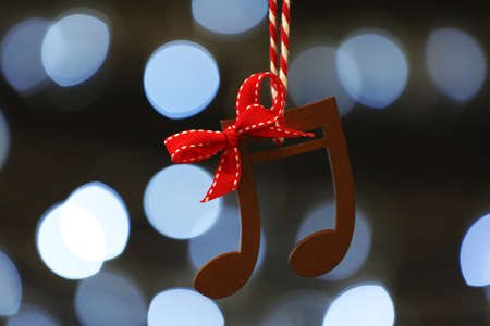 Photo for Wooden music notes against blurred Christmas lights - Royalty Free Image