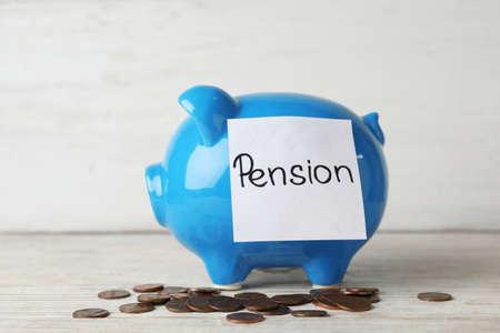 Photo pour Piggy bank with word PENSION and coins on table - image libre de droit