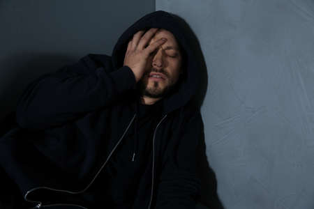 Passed out junkie after using drugs near grey wall