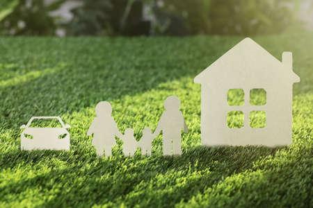 Foto de Paper cutout of family with house and car on fresh grass. Life insurance concept - Imagen libre de derechos
