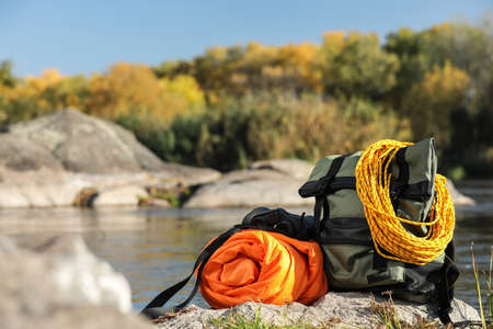 Photo for Set of camping equipment with sleeping bag on rock outdoors. Space for text - Royalty Free Image
