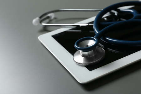 Stethoscope and tablet on table, closeup. Medical students stuff