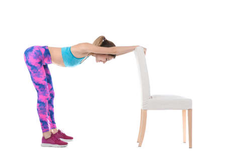 Foto de Young woman exercising with chair on white background. Home fitness - Imagen libre de derechos
