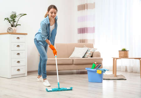 Photo pour Young woman washing floor with mop in living room. Cleaning service - image libre de droit