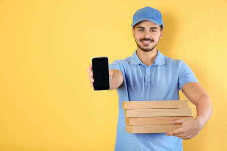 Photo pour Young man holding pizza boxes and smartphone on on color background, mockup for design. Online food delivery - image libre de droit