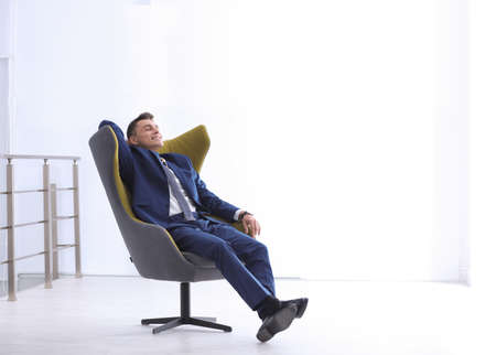 Photo pour Young businessman sitting in comfortable armchair indoors. Space for text - image libre de droit