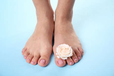 Photo pour Woman with smooth feet  and flower on color background, closeup. Spa treatment - image libre de droit