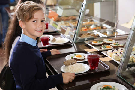 Foto de Cute boy near serving line with healthy food in school canteen - Imagen libre de derechos