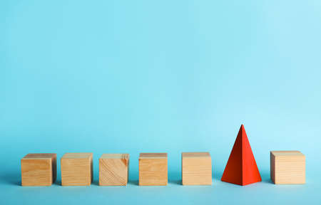 Photo pour Row of wooden cubes and red pyramid on color background. Be different - image libre de droit