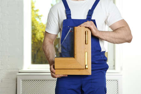 Photo pour Installation worker with sample of modern window profile indoors - image libre de droit