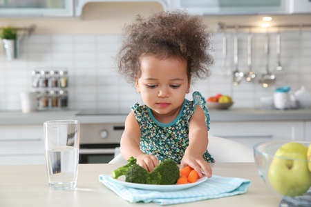 Photo pour Cute African-American girl eating vegetables at table in kitchen - image libre de droit