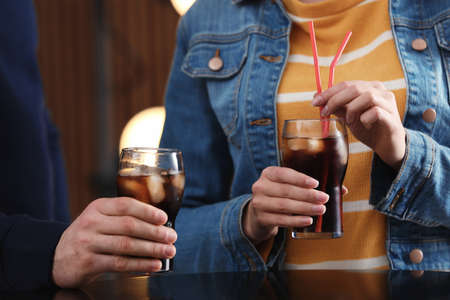People holding glasses of cola with ice on blurred background, closeupの写真素材