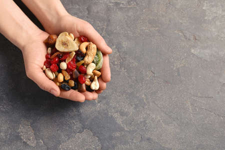 Woman holding handful of different dried fruits and nuts on color background, top view. Space for text