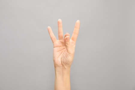 Woman showing number eight on grey background, closeup. Sign language