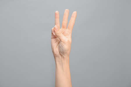 Woman showing number six on grey background, closeup. Sign language