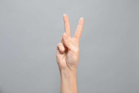 Woman showing number two on grey background, closeup. Sign language