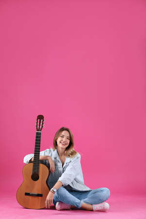 Young woman with acoustic guitar on color background