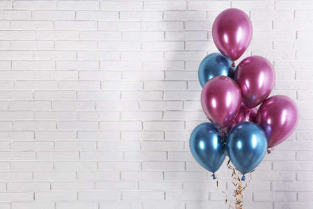 Photo pour Bright colorful balloons near brick wall, space for text. Party time - image libre de droit