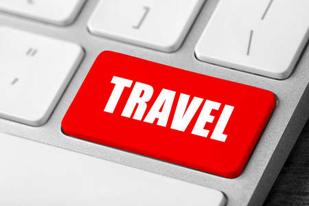 Computer keyboard with red button and word Travel. Tourist agency