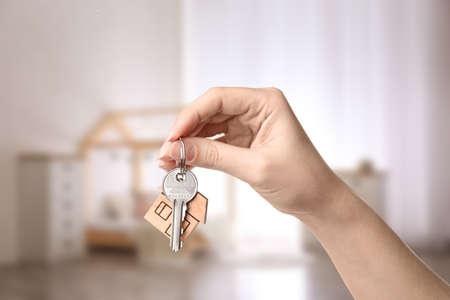 Photo pour Woman holding house key on blurred background, closeup - image libre de droit