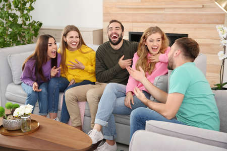 Group of friends telling jokes and laughing in living room