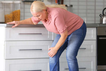 Senior woman suffering from knee pain in kitchen