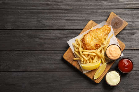 Foto de British traditional fish and potato chips on wooden background, top view with space for text - Imagen libre de derechos