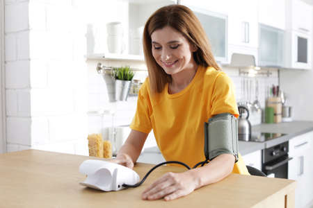 Photo for Woman checking blood pressure with sphygmomanometer at table indoors. Cardiology concept - Royalty Free Image