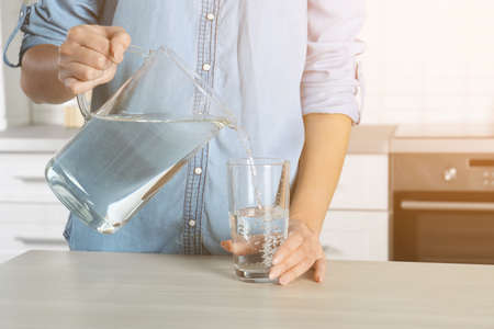 Foto de Woman pouring water into glass in kitchen, closeup. Refreshing drink - Imagen libre de derechos