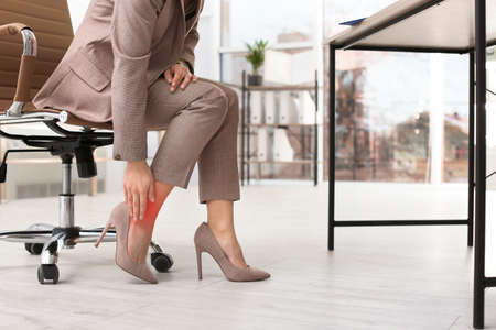 Photo pour Woman suffering from leg pain in office, closeup with space for text - image libre de droit