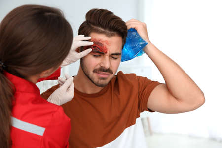 Photo for Nurse examining young man's head injury in clinic. First aid concept - Royalty Free Image