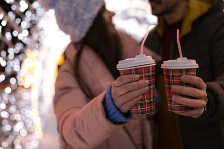 Photo pour Young couple with cups of mulled wine at winter fair, closeup - image libre de droit
