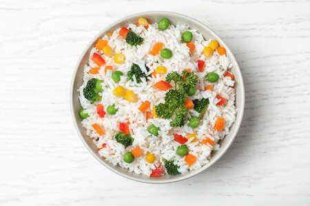 Foto de Bowl with tasty rice and vegetables on wooden background, top view - Imagen libre de derechos