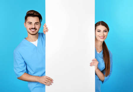 Medical students with blank poster on color background. Space for text